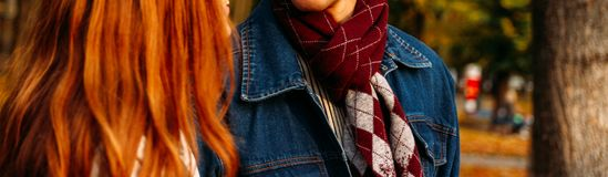 Red-haired girl and a guy in a denim jacket with a checkered scarf are walking in the autumn park, forest. close-up, brown scarf w royalty free stock photos