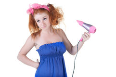 Red-haired girl with the hair dryer. Royalty Free Stock Photography