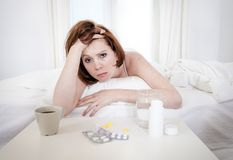 Red haired girl with hangover wanting coffee in bed. Red hair girl hungover wanting coffee and medication to help with her hungover in bed Royalty Free Stock Photo