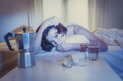 Red haired girl with hangover wanting coffee in bed Royalty Free Stock Images