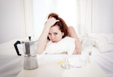 Red haired girl with hangover wanting coffee in bed Royalty Free Stock Photos