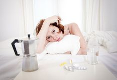 Red haired girl with hangover wanting coffee in bed Royalty Free Stock Photography