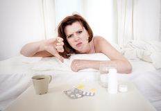 Red haired girl with hangover wanting coffee in bed Stock Photography