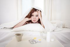 Red haired girl with hangover wanting coffee in bed. Red hair girl hungover wanting coffee and medication to help with her hungover in bed Royalty Free Stock Photos