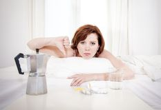Red haired girl with hangover wanting coffee in bed Stock Image