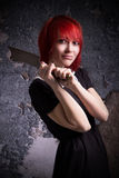 Red-haired girl has an ax stock image