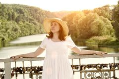 Red-haired girl in hat posing against background of river and green forest Stock Photography