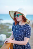 Red-haired girl in a hat and sunglasses Royalty Free Stock Images