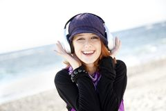 Red-haired girl with headphone on the beach. Royalty Free Stock Photography