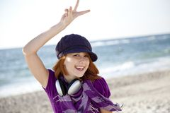 Red-haired girl with headphone on the beach. Stock Photography