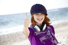 Red-haired girl with headphone on the beach. Stock Photos