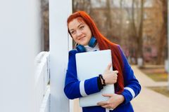 Red-haired girl with headphones in a blue coat in autumn park dreams and hugs a laptop stock image
