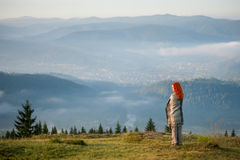Red-haired girl on a hill against beautiful mountain landscape Royalty Free Stock Images