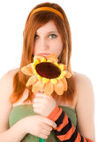 Red haired girl holding big smiling flower Stock Image