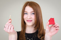 Red-haired girl holding a key and house. Girl holds in one hand a key, in the other hand a house and smiling Stock Photo