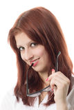 Crafty sight. The red-haired girl holds glasses and smiles Royalty Free Stock Photography