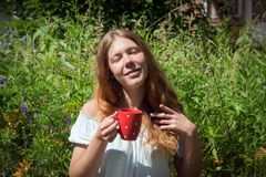 Red-haired girl holds in her hand a red mug with tea on the background of green grass in the summer royalty free stock image