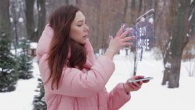Red-haired girl with hologram Buy house. Beautiful young woman in a winter park interacts with HUD hologram with text Buy house. Red-haired girl in warm pink stock footage