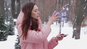 Red-haired girl with hologram Sales target. Beautiful young woman in a winter park interacts with HUD hologram with text Sales target. Red-haired girl in warm stock video footage