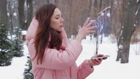 Red-haired girl with hologram satellite. Beautiful young woman in a winter park interacts with HUD hologram satellite. Red-haired girl in warm pink clothes uses stock footage
