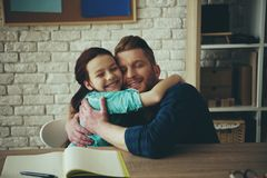 Red haired girl hugs happy father sitting at table. Child education concept. Fatherhood stock photography