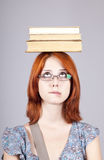 Red-haired girl keep books on her head. Stock Photo
