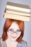Red-haired girl keep books on her head. Royalty Free Stock Photos