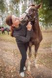 Red-haired girl kisses her favorite horse