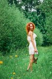 Red-haired girl in a lace dress in a clearing in a green park. By the strap she holds a retro camera