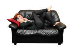 Red-haired girl is laying on sofa Stock Photography