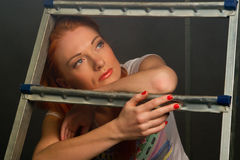 Red-haired girl leaning on a ladder Royalty Free Stock Photo