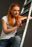 Red-haired girl leaning on a ladder Stock Image