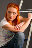 Red-haired girl leaning on a ladder Stock Photos