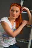 Red-haired girl leaning on a ladder Stock Images
