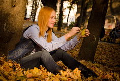 Red haired girl with leaves in a park Royalty Free Stock Photo
