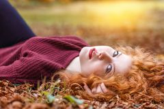 Red-haired girl lies in the fallen yellow foliage royalty free stock images