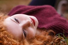 Red-haired girl lies in the fallen yellow foliage royalty free stock photography