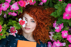 Red-haired Girl lies in wild flowers. Royalty Free Stock Images