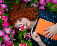 Red-haired girl lies in wild flowers. royalty free stock photos