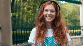 Ginger girl listening to music in big headphones stock images