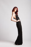 Red-haired girl in long black evening dress. Beautiful red-haired girl in long black evening dress studio shot stock photo
