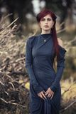 Red-haired girl in a long blue dress. In the forest royalty free stock photography