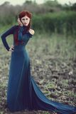 Red-haired girl in a long blue dress. In the forest royalty free stock image