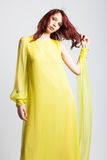 Red-haired girl in long elegant yellow dress Royalty Free Stock Photography
