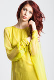Red-haired girl in long elegant yellow dress Royalty Free Stock Photo