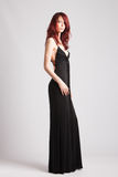 Red-haired girl in long evening black dress. Young attractive red-haired girl in long black evening dress studio shot stock images
