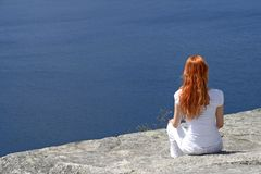 Red-haired girl looking over blue water Royalty Free Stock Image