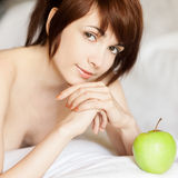 Red-haired girl lying with apple Royalty Free Stock Photos