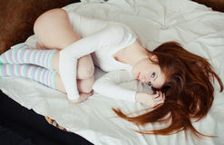 Red-haired girl lying on the bed Stock Photography