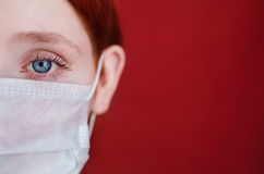 Red-haired girl with a medical mask on a red background, woman d Royalty Free Stock Photo